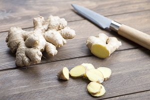 Ginger next to kitchen knife on wooden table. Food