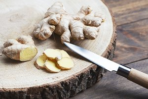 Ginger next to kitchen knife on wood. Food