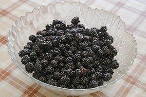 Plate with berries black blackberries. Fruits berries on the table