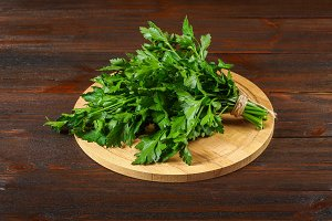 A bunch of green parsley on a wooden table.