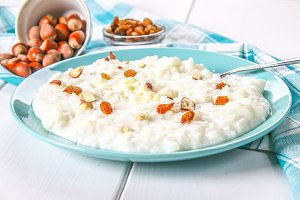 Rice milk porridge with nuts and raisins in a blue dish on a white wooden table.
