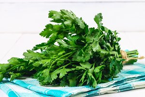 A bunch of green parsley on a white wooden table.