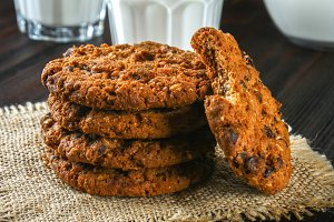 Homemade oatmeal cookies. A stack of cookies on burlap on a brown wooden table. Milk in the background.