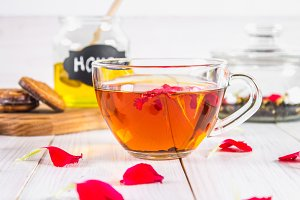 Floral black tea, honey can, petals on a white wooden table.