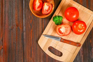 Fresh red tomatoes and sliced halves with cilantro on a wooden table. Top view.