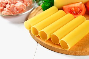 Italian pasta cannelloni. Raw tube for stuffing stuffing surrounded by ingredients for cooking, parmesan cheese, tomato, minced meat on a white wooden table.