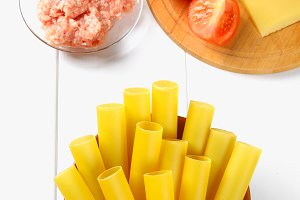 Italian pasta cannelloni. Raw tube for stuffing stuffing surrounded by ingredients for cooking, parmesan cheese, tomato, minced meat on a white wooden table. Top view. Copy the space.
