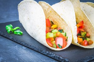 Traditional Mexican tacos with meat and vegetables on wooden background.