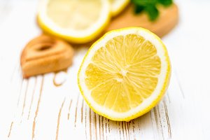 Lemons on a board on a white wooden background.