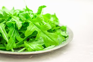 Fresh juicy leaves of arugula on a light concrete background.