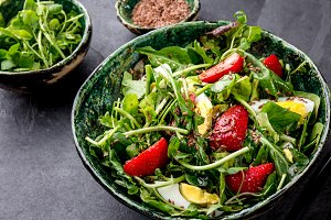 Green leaves and srawberry salad with linen seeds in green bowl, gray background