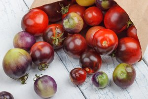 Different tomatoes in the paper bag on the white wooden background