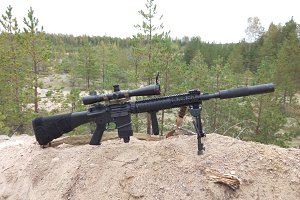 Assault rifle on the background of pine forests and sand