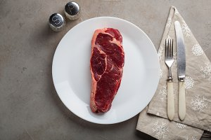 Raw beef marbled steak with vintage white utensils on old stone background. A piece of meat with pepper and salt on the table. Steak New York. Top view