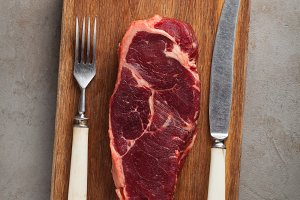 Raw beef marbled steak with vintage white Cutlery on old stone background. A piece of meat on a wooden Board. Steak New York. Top view with copy space
