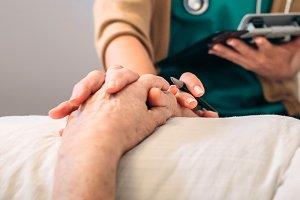 Female doctor comforting older patient