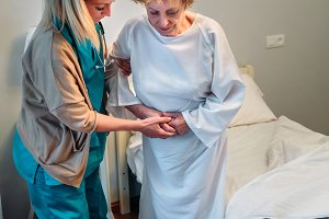 Caregiver helping elderly patient to stand up