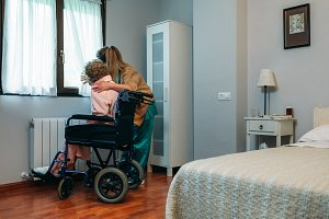 Caregiver showing the view through the window to elderly patient