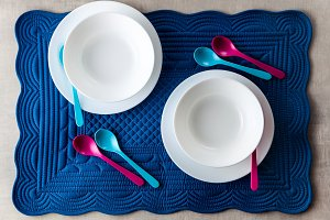 A set of baby dishes on a blue soft