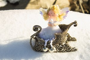 A toy angel sits in a golden sleigh on the snow. Christmas toys.