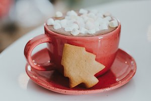 A cocoa drink in a clay mug on a shabby wooden background. A porcelain cup of black coffee with white marshmallows.