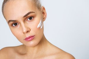 Woman with cosmetic cream on a face