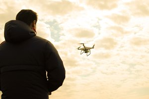 A man with a remote control in his hands. Controlling the flight of the drone against the sky. Phantom.