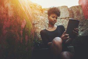 Black girl with digital pad on stair