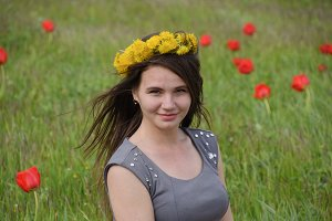 A girl with a wreath of dandelions on her head. Beautiful fairy young girl in a field among the flowers of tulips.