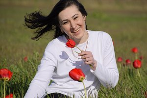 Beautiful fairy young girl in a field among the flowers of tulips. Portrait of a girl on a background of red flowers and a green field. Field of tulips