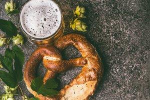 Mug of beer and pretzel with hops