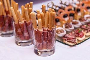 bread sticks with a prosciutto in a glass