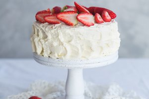 White cream cake with strawberry on the white table