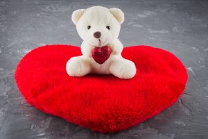 White toy teddy bear with heart on a gray background. The symbol of the day of lovers. Valentine's Day. Concept February 14.