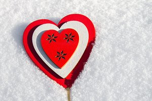 In the snow lies a red heart made of wood. Template for a holiday card with a white texture and free space for text.