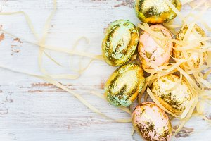 Golden Easter Eggs on white wooden background