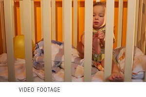 Kid sits in a playpen.