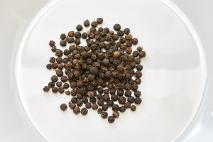 Black pepper corns on white backgrou
