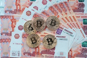Coins bitcoin, lie on a bill of 5000 thousand rubles. The banknotes are spread out on the table in a free order.