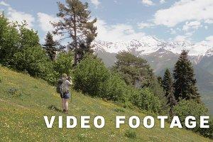 Youn woman takes a picture in the mountains - Mestia, Georgia