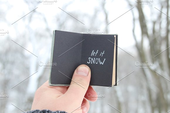 Let it snow lettering and Falling snow. Vintage book with inscription