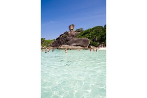 Island with Sailing Boat Rock in Similan National park, Phang Nga, Thailand. Tourists arrive by boat and to walk through the waves to the beach