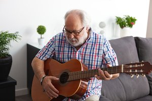 Retired man playing guitar