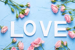 Word love and pink roses