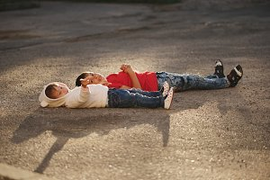 boy and girl lying on asphalt