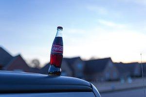 Coke bottle sitting on a car