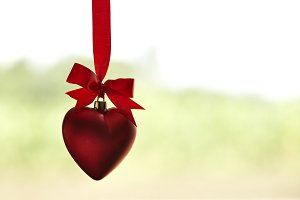 red hearts on ribbon green backgroun