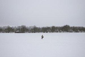 Boy Walking Through Snowy Field