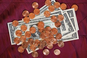 Dollar notes and coin, United States over red velvet background