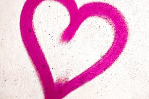 Pink heart on concrete wall